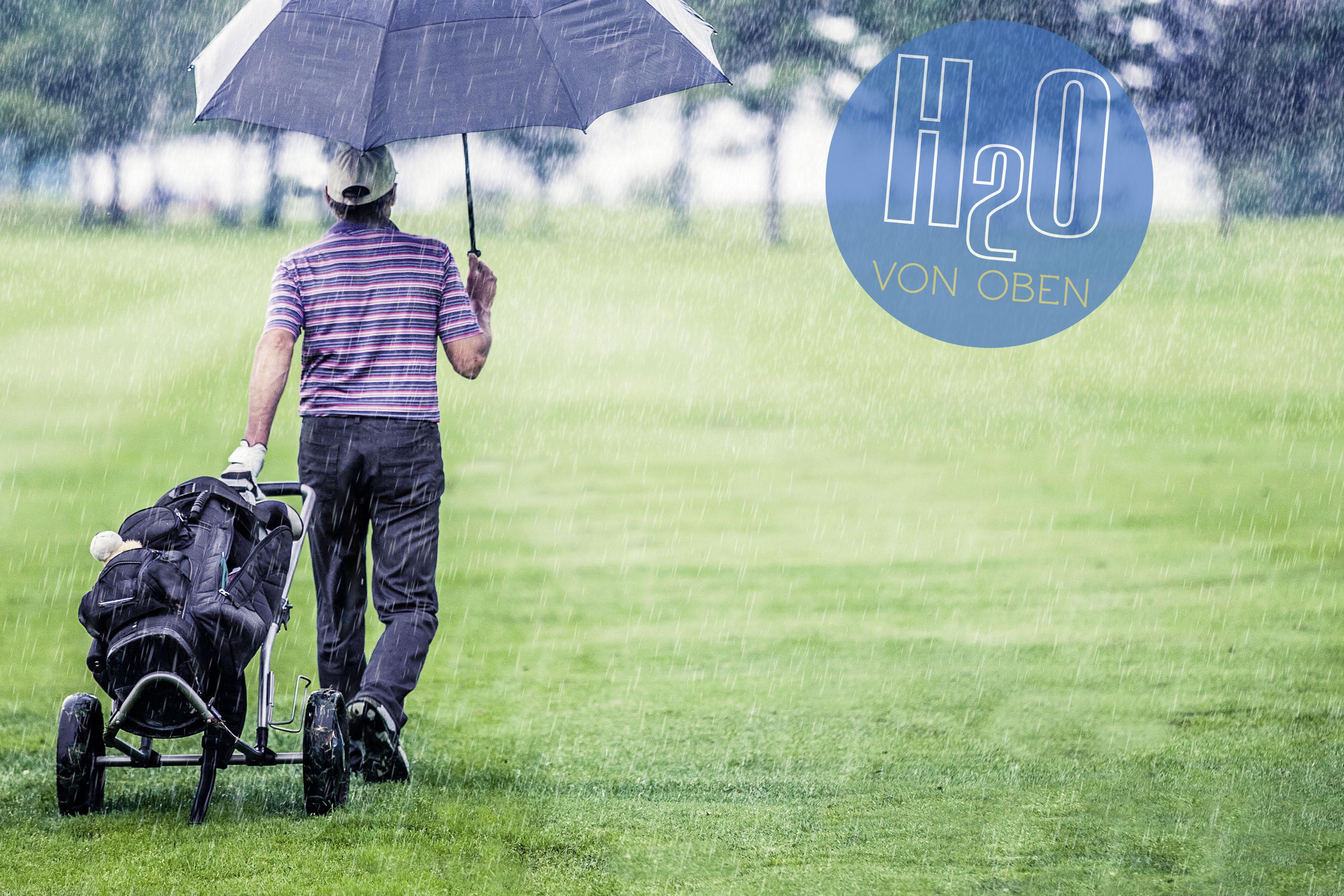 Mann geht im Regen über den Golfplatz