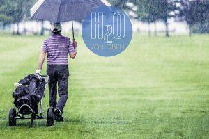 Golfer geht im Regen über den Rasen