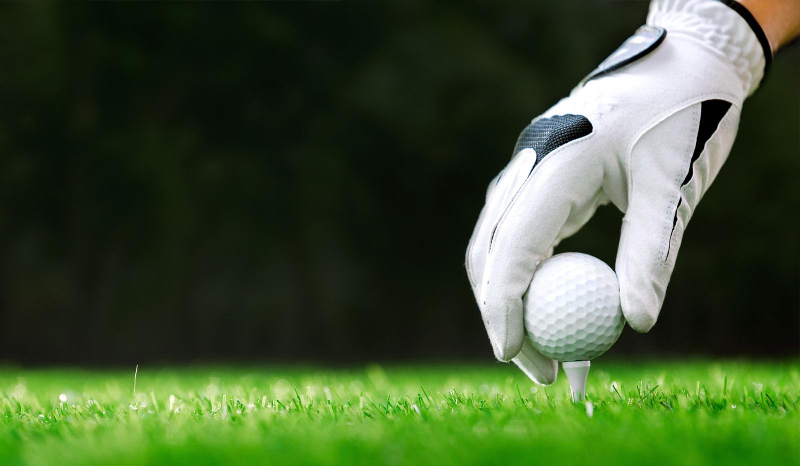 Golfball wir auf ein Tee gesetzt