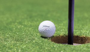 Golfball an der Kante vom Loch