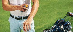 Auftragen von Sonnenspray beim Golfen