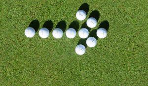 Pfeil nach rechts aus Golfbällen auf dem Rasen