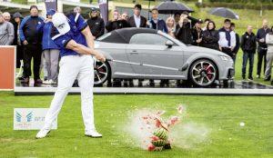 Golfer schlägt einen Ball durch eine Melone