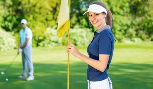 Frau hält Fahne auf Golfplatz.