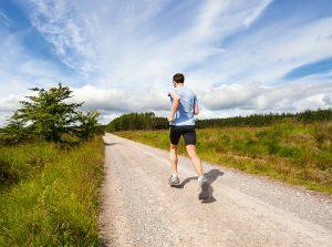 Mann joggt auf Feldweg.