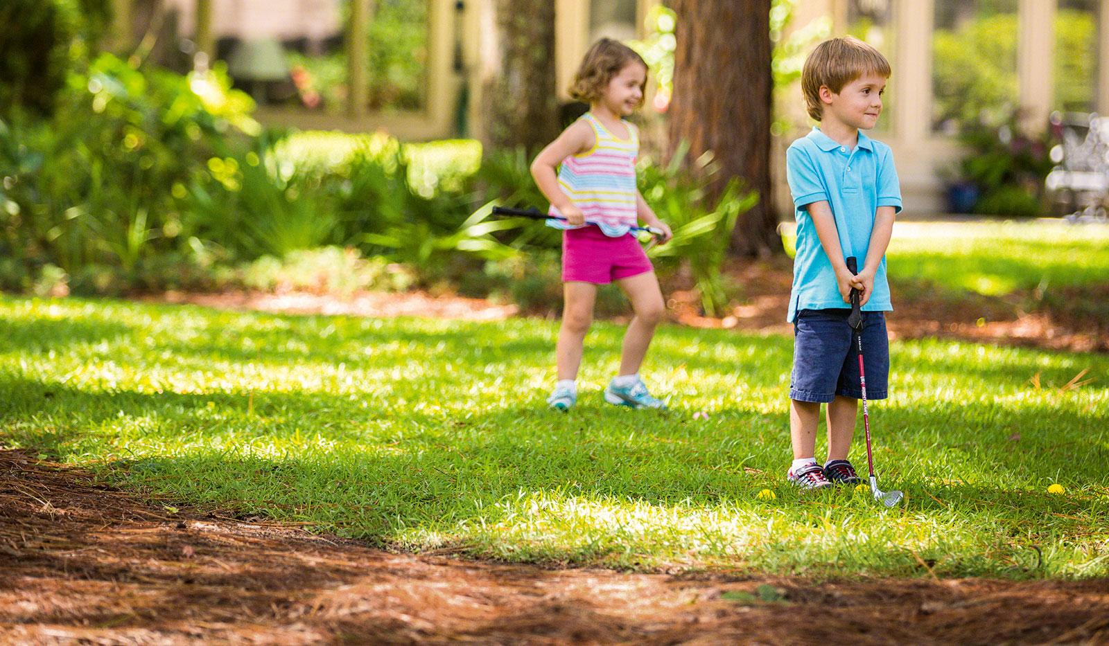 Kinder spielen Golf im Garten