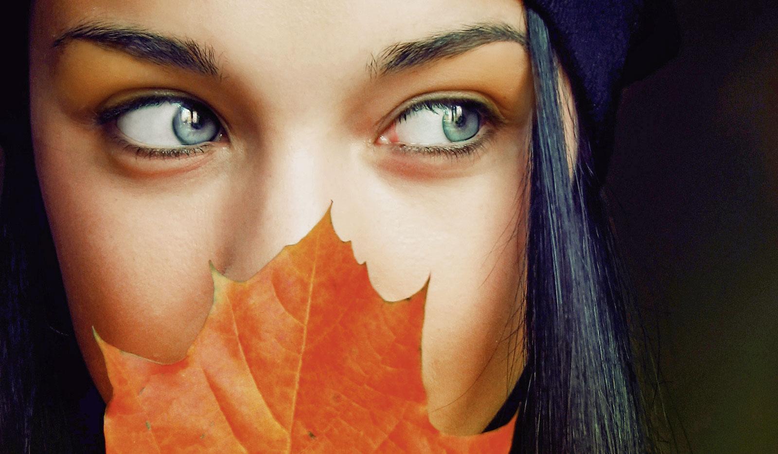 Frau mit Herbstblatt vor dem Gesicht