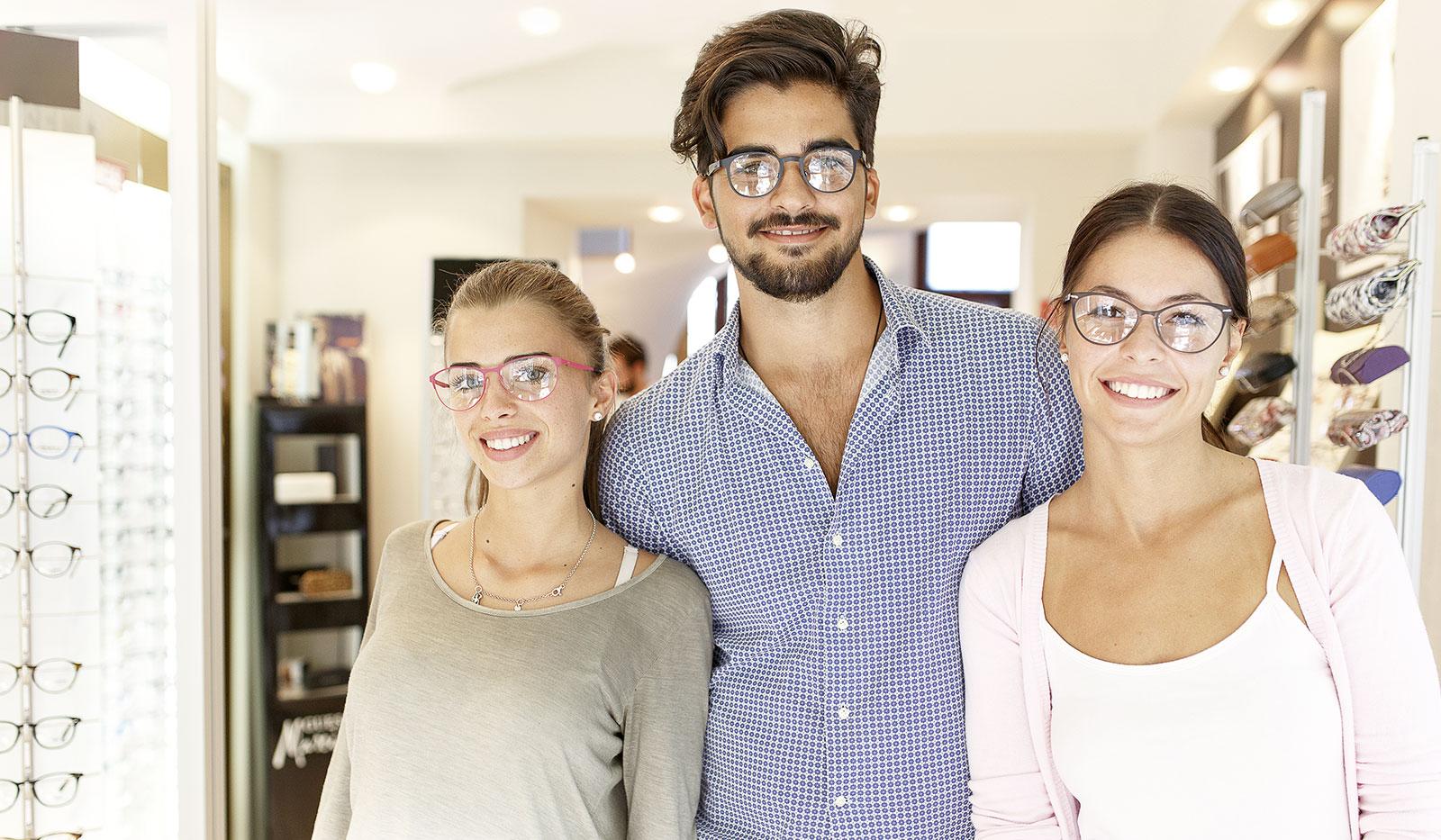 Frauen und Mann tragen Brillen im Brillengeschäft