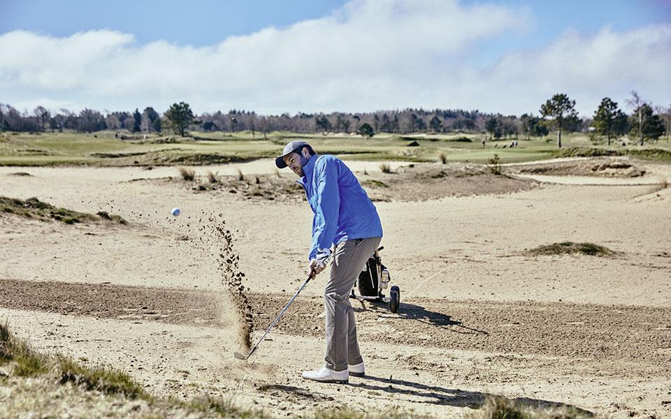 jan Hartmann schlägt Golfball aus dem Bunker