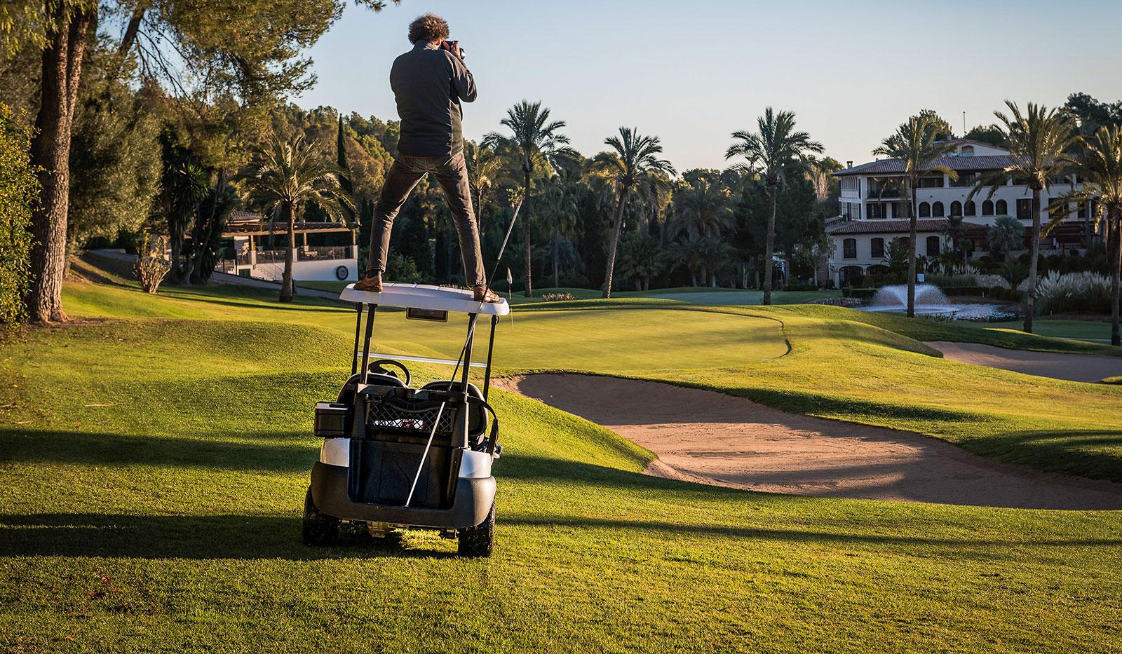 Fotograf steht auf Golfcart