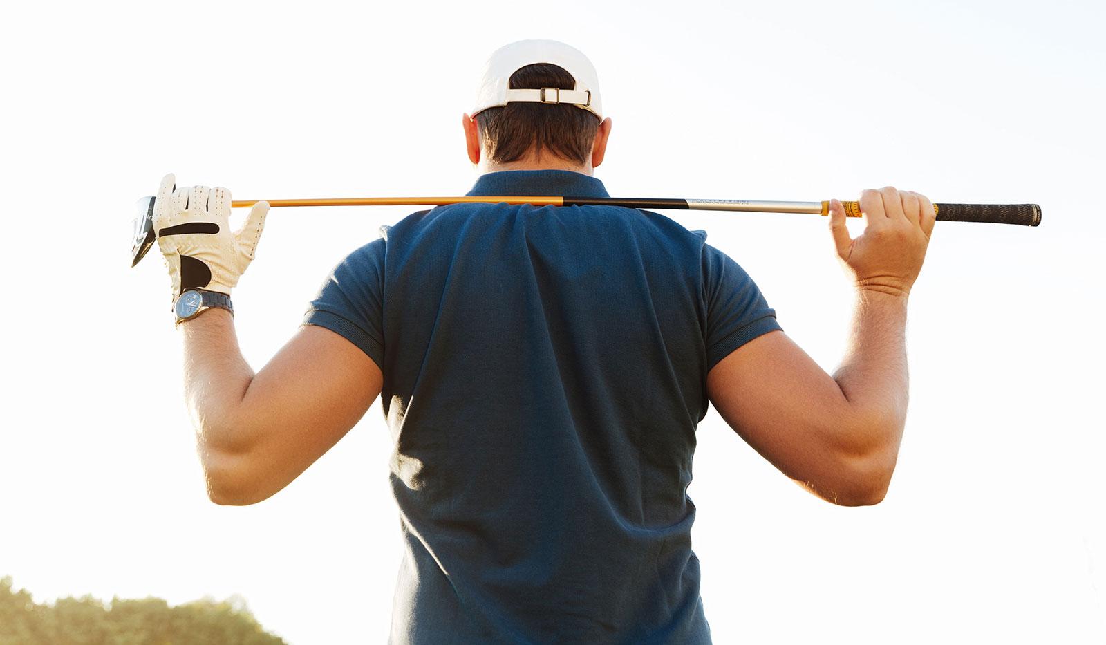 Golfer stretcht seinen Rücken mit Golfschläger