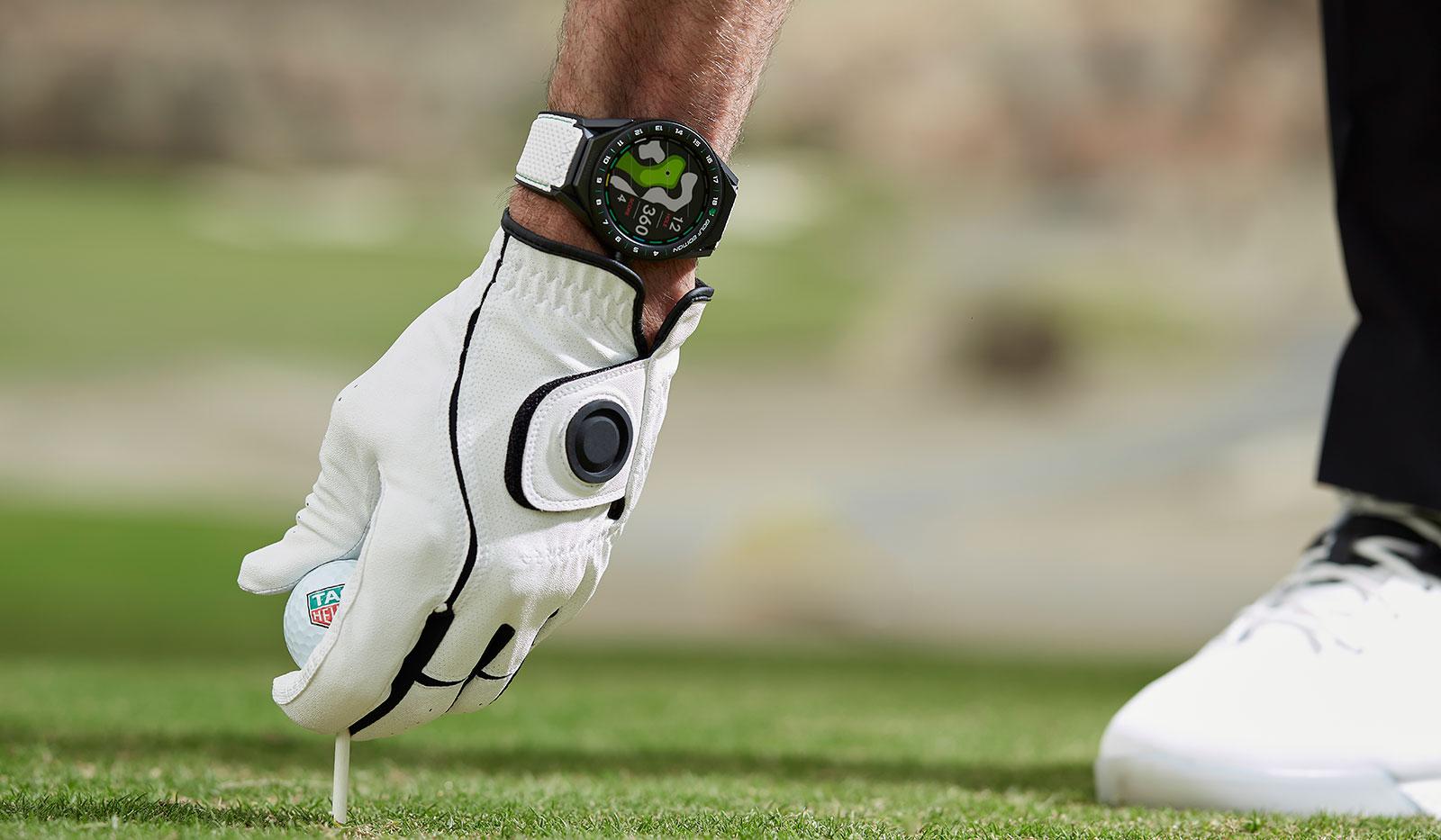 Golfer platziert Golfball auf Tee und trägt eine TAG Heuer Connected Modular 45 Golf Edition Smartwatch