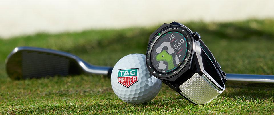 TAG Heuer Smartwatch. TAG Heuer Golfball, Golfschläger im Hintergund