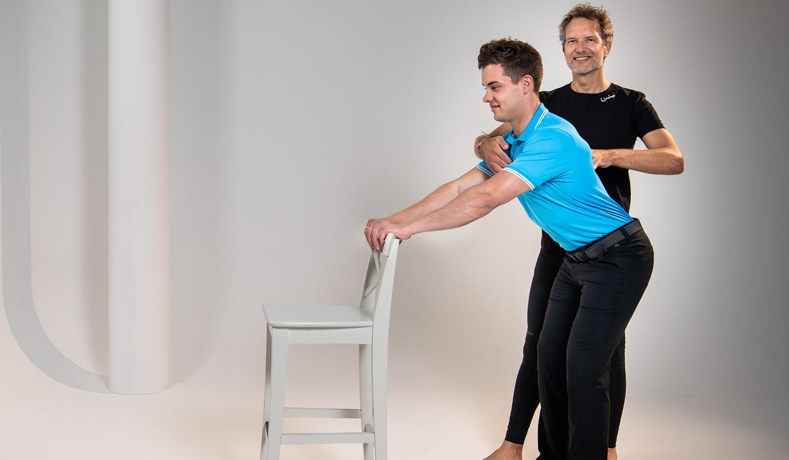 Pilatesübung: Sven Dyhr stützt sich auf Stuhllehne und Christian Lutz stabilisiert ihn