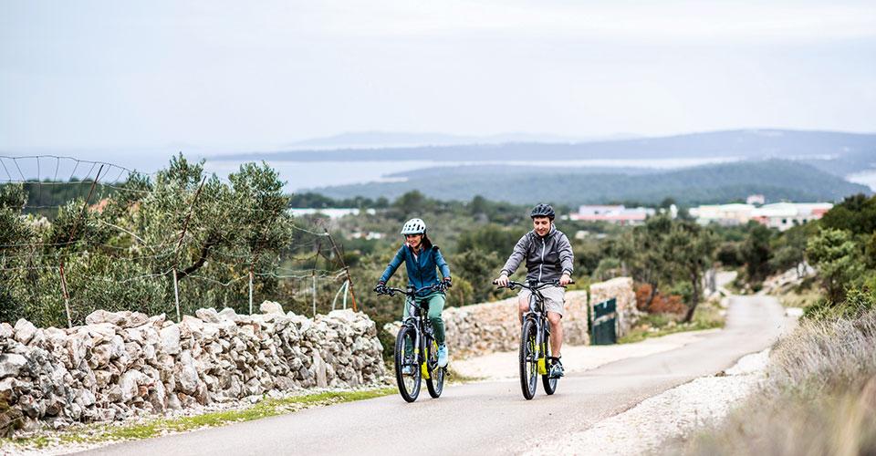Paar fährt mit E-Bikes auf einer ländlichen Straße