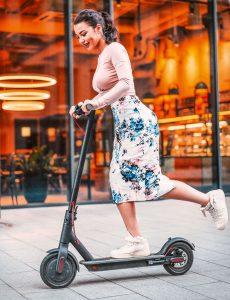 Frau fährt mit E-Scooter