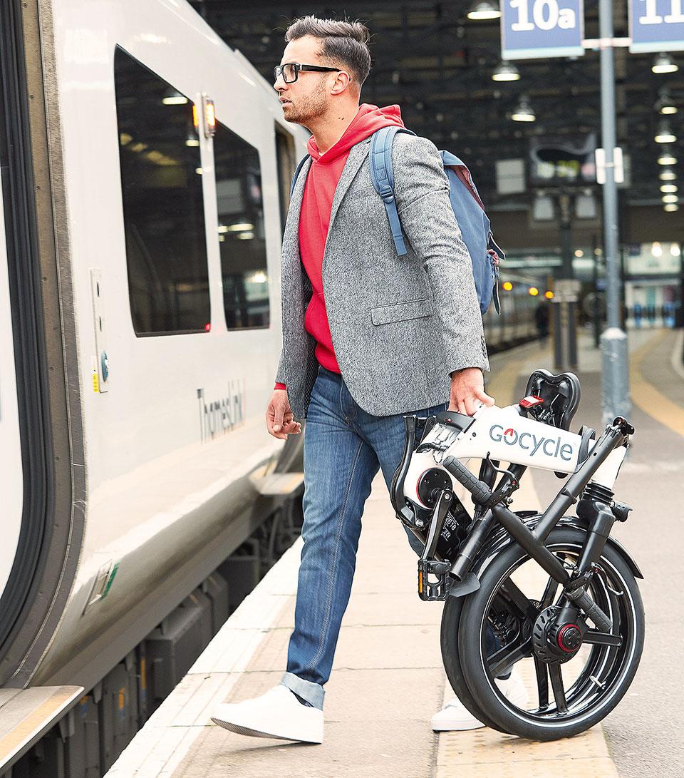Mann steigt mit faltbarem E-Bike in einen Zug