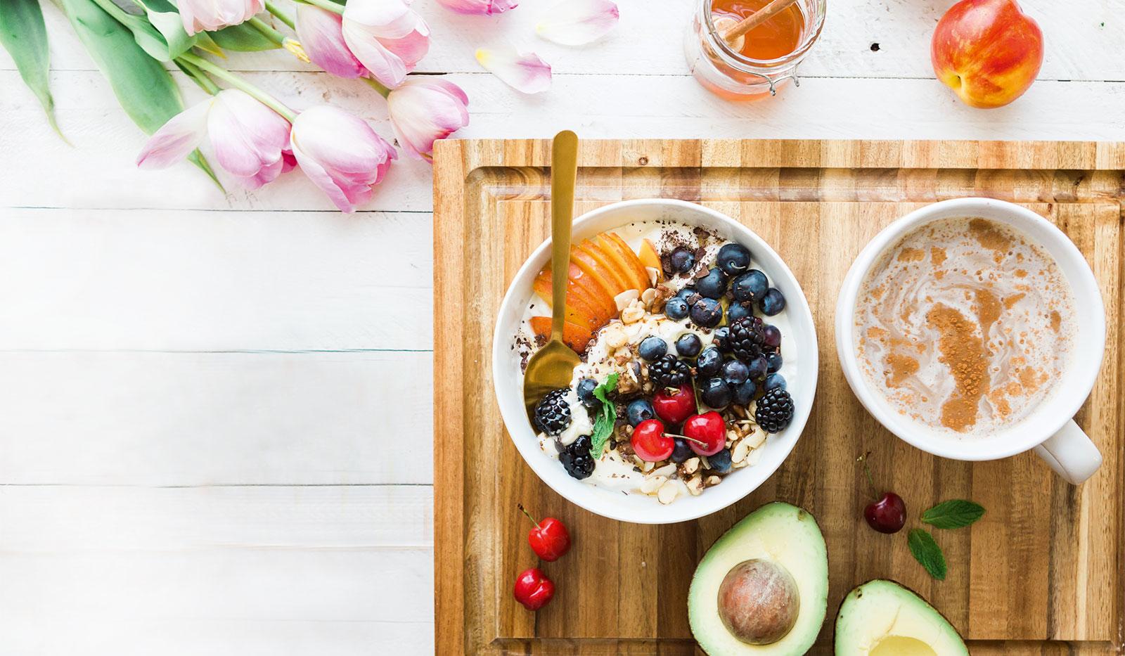 Frühstückstisch mit Schüssel Müsli mit Früchten und Tasse Tee