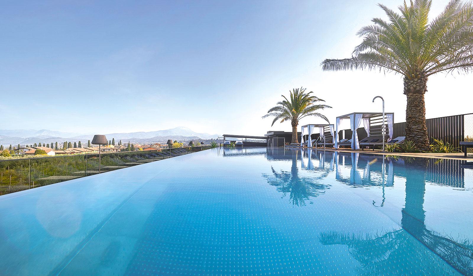 Außenpool umgeben von Palmen des Quellenhof Luxury Resorts Gardasee