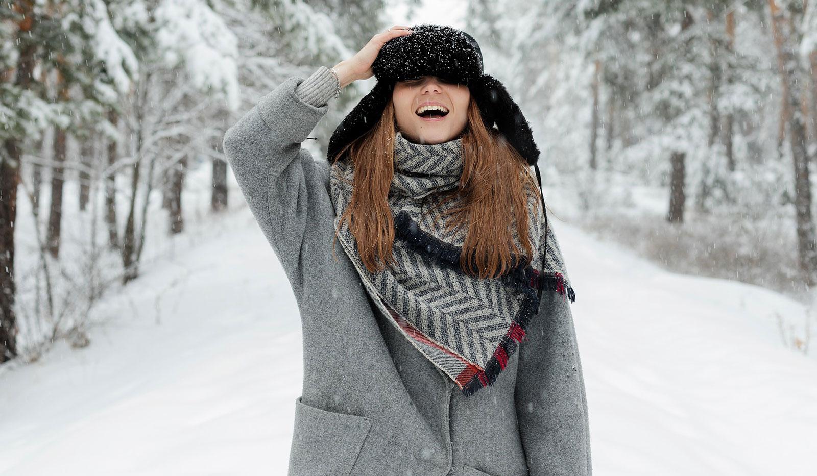 Junge Frau mit dicken Winterklamotten steht auf Feldweg im Winter
