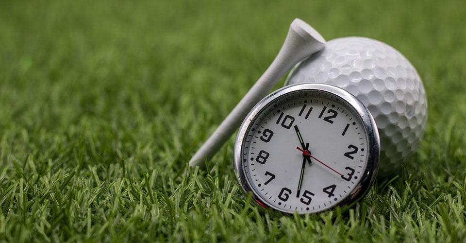 Golfball, Tee und Zeituhr auf Rasen