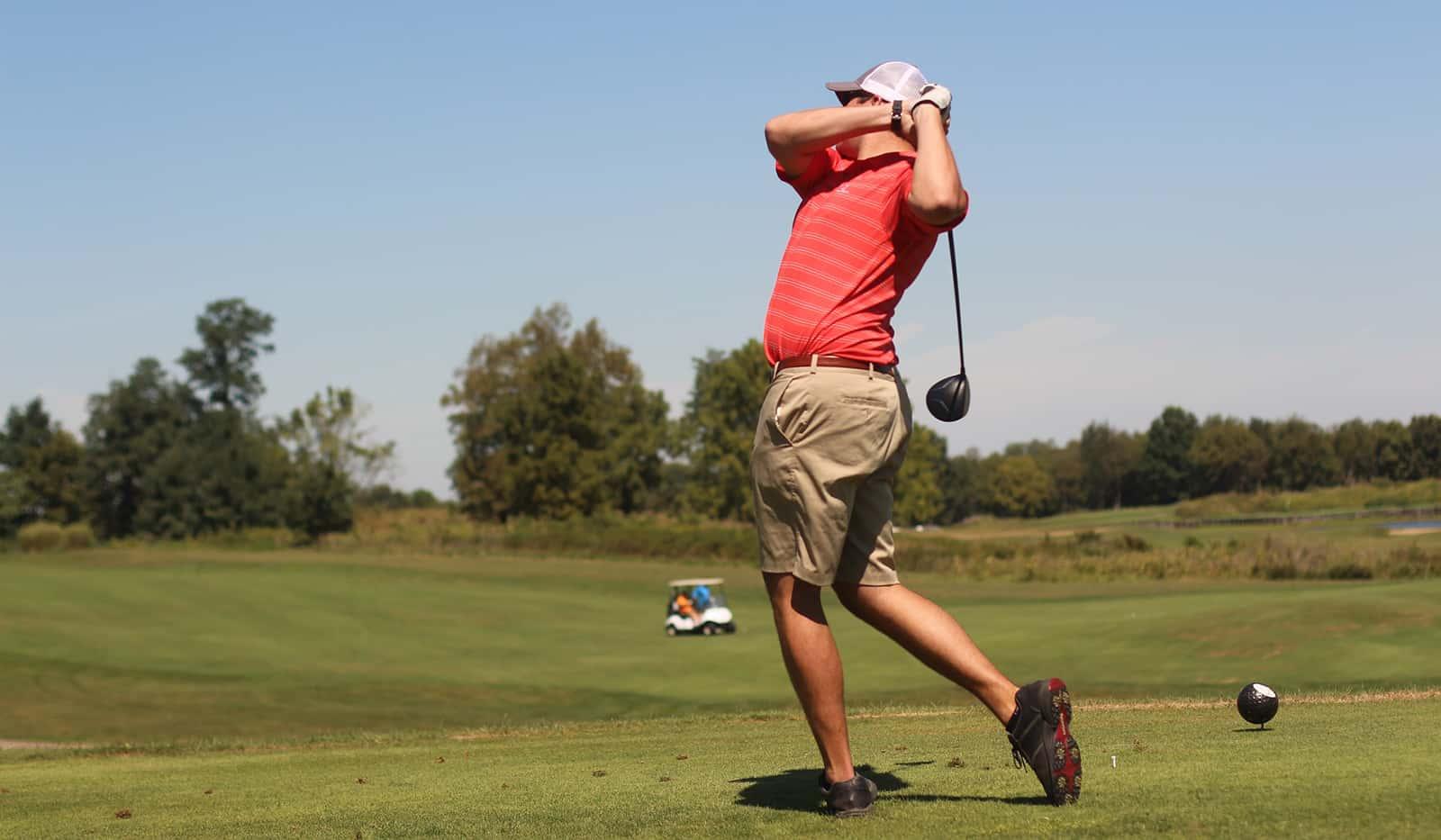 Man auf dem Golfplatz Abschlag