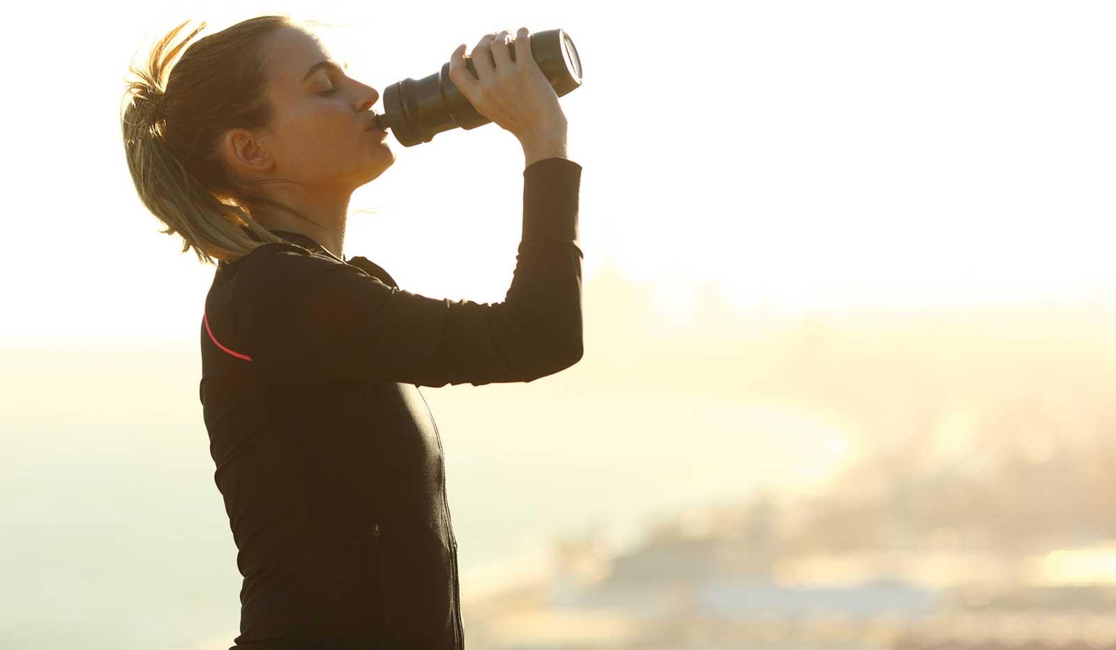Frau in Sportklamotten trinkt aus Trinkflasche
