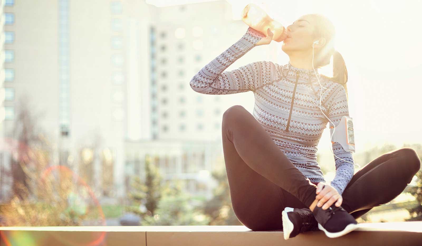 Frau in sportlicher Kleidung trinkt aus Trinkflasche