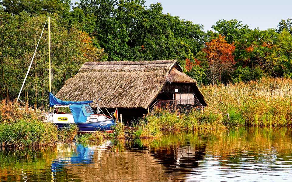 See mit Haus und Segelboot