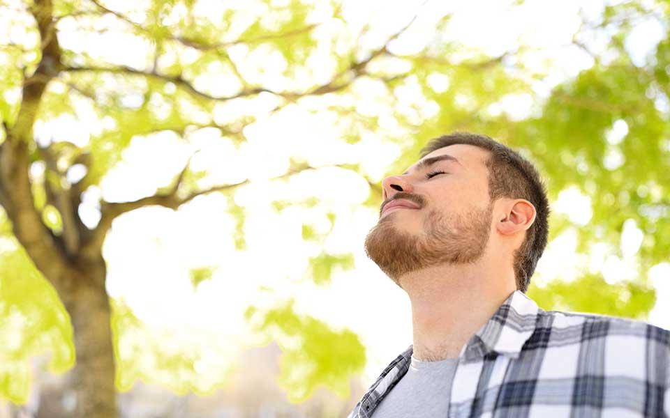 Mann, der Gesicht in die Sonne hält
